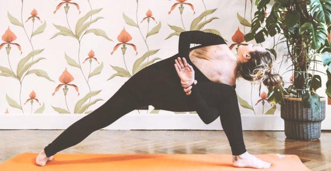 Posizione del triangolo esteso con mani incrociate dietro la schiena